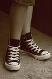 De voeten van het meisje in tegenovergestelde tennisschoenen stock afbeelding