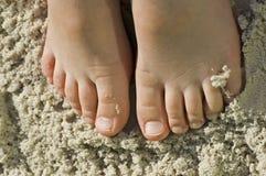 De voeten van jonge geitjes in zandige strandpret stock afbeeldingen
