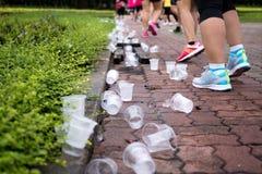 De voeten van marathonagenten en emptry waterkoppen op verfrissingpunt Stock Afbeelding