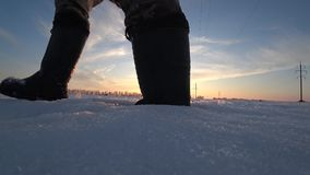 De voeten van mensen in warme rubber het werklaarzen gaan in diepe sneeuw bij zonsondergang op een de winter zonnige dag stock video