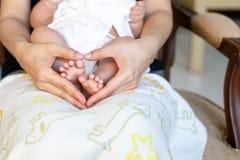 De voeten van de pasgeboren baby op Moeders dienen gestalte gegeven hart, Familie en Liefdeconcept in royalty-vrije stock foto's