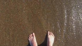 De voeten van de toerist zijn op de kiezelstenen zij door kleine golven met schuim worden gewassen Rust door het overzees stock videobeelden