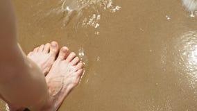 De voeten zijn op het zand dichtbij het water Strand De zonnige dag van de zomer stock videobeelden