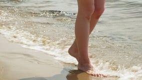 De voeten zijn op het zand dichtbij het water Strand De zonnige dag van de zomer stock video