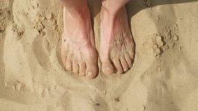De voeten zijn op het zand dichtbij het water Strand De zonnige dag van de zomer stock footage
