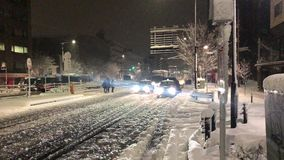 De voetgangers en het verkeersstrijd van Tokyo tijdens een zeldzaam sneeuwonweer stock footage