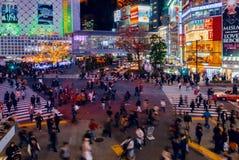 De voetgangers kruisen bij Shibuya-Kruising Het is één van de beroemdste wereld door elkaar gooit zebrapadden Stock Afbeeldingen