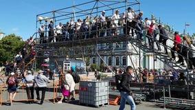 De voetgangers kruisen de tijdelijke brugweg van de marathon in St. Petersburg Veiligheid van atleten tijdens de concurrentie stock videobeelden