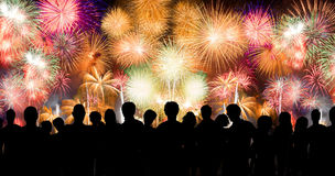 De volkeren in silhouet genieten van lettend op verbazend vuurwerk Stock Afbeeldingen