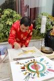 De volkskunstenaar in rood zweempjekostuum maakt het traditionele Chinese suiker schilderen Royalty-vrije Stock Afbeelding