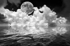 De volle maan en de wolken in de donkere hemel van de fantasienacht dachten in golvend oceaanwater na Stock Fotografie