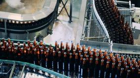 De volledige bierflessen bewegen zich langs de metaalfabriekstransportband stock videobeelden