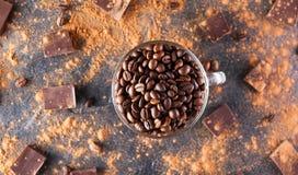 De volledige glaskop Geroosterde koffiebonen op de donkere steenachtergrond met verdrijft cacao, stukken van chocolade en bonen s Stock Foto's