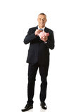 De volledige holding van de lengte vrolijke zakenman piggybank Stock Afbeelding