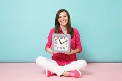 De volledige jonge vrouw van het lengteportret in het roze witte de broek van de overhemdsblouse zitten op de klok van de vloergr stock foto