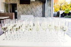 De volledige koude tribune van champagnefluiten tussen emmers op dinerlijst royalty-vrije stock foto's