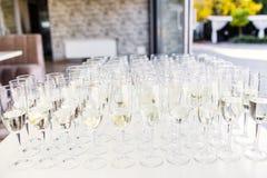 De volledige koude tribune van champagnefluiten tussen emmers op dinerlijst stock fotografie