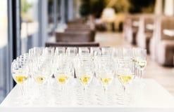 De volledige koude tribune van champagnefluiten tussen emmers op dinerlijst stock foto