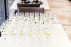 De volledige koude tribune van champagnefluiten tussen emmers op dinerlijst stock afbeeldingen