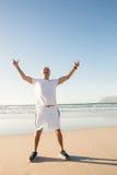 De volledige lengte van de hogere mens met wapens hief status op zand tegen duidelijke hemel op Stock Foto