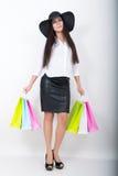 De volledige lengte van een mooie jonge Aziatische dame in een witte blouse en het zwarte leer begrenzen holdings kleurrijke zakk Royalty-vrije Stock Afbeeldingen