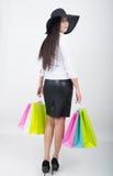 De volledige lengte van een mooie jonge Aziatische dame in een witte blouse en het zwarte leer begrenzen holdings kleurrijke zakk Royalty-vrije Stock Afbeelding