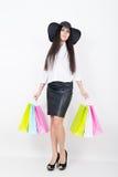 De volledige lengte van een mooie jonge Aziatische dame in een witte blouse en het zwarte leer begrenzen holdings kleurrijke zakk Stock Afbeeldingen