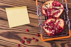 De volledige mand van de metaalmarkt van de helften rode rijpe verse granaatappel en verspreide zaden stock afbeeldingen