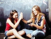 De volta à escola após férias de verão, duas meninas reais adolescentes na sala de aula com o quadro-negro pintado junto fotos de stock royalty free