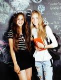 De volta à escola após férias de verão, duas meninas reais adolescentes na sala de aula com o quadro-negro pintado junto, estilo  fotografia de stock