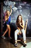 De volta à escola após férias de verão, duas meninas adolescentes na sala de aula com o quadro-negro pintado imagem de stock