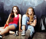 De volta à escola após férias de verão, duas meninas adolescentes na sala de aula com o quadro-negro pintado junto imagem de stock