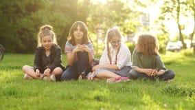 De volta à escola, estudantes após a escola Colegas alegres e amigáveis que conversam ao sentar-se na grama no parque filme