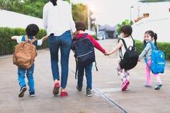 De volta à escola indo do grupo da mãe dos estudantes da escola junto pare imagem de stock