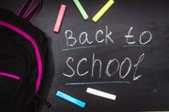 De volta à mensagem da escola no quadro-negro inscreido com giz colorido para o fundo backpack Fotos de Stock