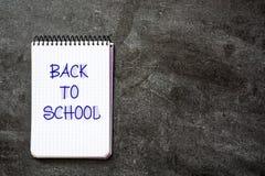 ` De volta à mensagem do ` da escola escrita em um caderno no fundo da ardósia Foto de Stock