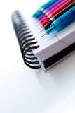 De volta às fontes de escola, às multi penas coloridas e a um noteboo espiral foto de stock