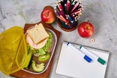 De volta ao conceito da escola, as fontes de escola, biscoitos, embalaram o almoço e a cesta de comida sobre o quadro branco, foc fotografia de stock
