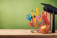 De volta ao conceito da escola com carrinho de compras, livros e chapéu da graduação foto de stock