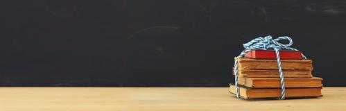 De volta ao conceito da escola pilha de livros sobre a mesa de madeira na frente do quadro-negro imagens de stock royalty free