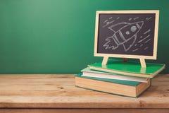 De volta ao fundo da escola com livros, esboço do quadro e do foguete foto de stock royalty free