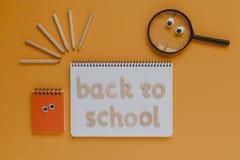 De volta ao material da escola, caderno com espaço da cópia no meio Fundo alaranjado Foto de Stock