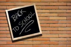 De volta ao quadro-negro da escola na parede de tijolo foto de stock