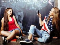 De volta ? escola ap?s f?rias de ver?o, duas meninas adolescentes na sala de aula com o quadro-negro pintado junto foto de stock