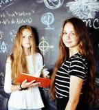 De volta ? escola ap?s f?rias de ver?o, duas meninas adolescentes na sala de aula com o quadro-negro pintado junto fotos de stock royalty free