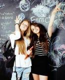 De volta ? escola ap?s f?rias de ver?o, duas meninas adolescentes na sala de aula com o quadro-negro pintado junto foto de stock royalty free