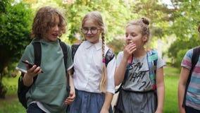 De volta ? escola As crianças vão educar e para ter o divertimento que fala, a estudante encaracolado mostra seu smartphone aos c video estoque