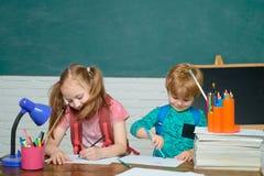 De volta ? escola e ao tempo feliz A crian?a est? aprendendo na classe no fundo do quadro-negro Menino pré-escolar pequeno bonito fotografia de stock royalty free