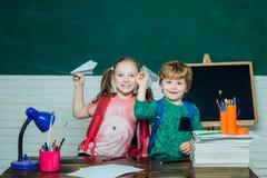 De volta ? escola e ao tempo feliz Menino inteligente bonito feliz e menina bonito com o avião de papel do brinquedo Primeira vez foto de stock