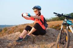De volwassen aantrekkelijke vrouwelijke fietser zit op de rots en maakt p Royalty-vrije Stock Afbeeldingen